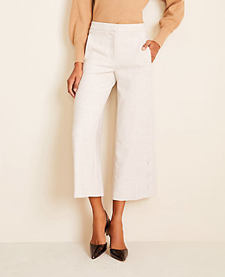 Tailored with apron side pockets that lay flat for an extra flattering look, this wide leg pair steps out with a polished button hem. Front zip with hook-and-bar closure. Front vertical on-seam pockets. Back welt pockets.