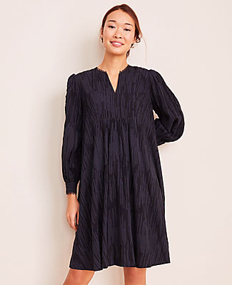 In a textured dobby weave, this softly shirred dress looks sharp and gets the job done in style. Split neck. Long sleeves with button cuffs. Bib front with shirring beneath. Back yoke with shirring beneath. Lined body.