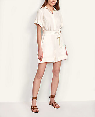 Cinched with a flattering tie waist, our short sleeve romper has an easy, flattering drape that\'s perfect for the season. Point collar. Short sleeves. Hidden button front. Smocked waistband. Self tie belt. Front off-seam pocket. Lined shorts.