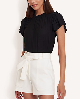 Delicately spotted, smocked and ruffled, this sweet top is a truly fresh pick. Ruffle jewel neck. Flutter sleeves. Smocked front shoulder yoke with shirring beneath. Back slit with button closure. Ann Taylor Spotted Smocked Ruffle Top