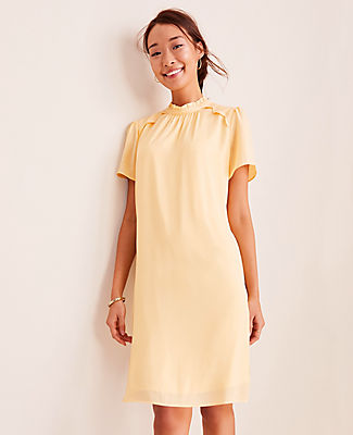 Refined lace trim adds romantic edge to our ruffle collar shift dress. Shirred jewel neck with ruffle collar. Short sleeves with shirred sleeve caps. Back slit with button closure. Lined body.