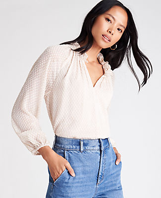 Get ruffled up and ready to go in this of-the-moment top, styled in a softly shirred silhouette. Tunneled elastic ruffle neck with front slit and button closure. Long raglan sleeves with elasticized cuffs. Lined body. Ann Taylor Clip Shirred Raglan Sleeve Top